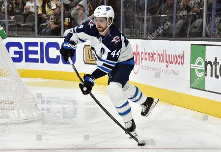 Winnipeg Jets defenseman Josh Morrissey (44) skates with the puck against the Vegas Golden Knights during the second period of an NHL hockey game, in Las Vegas