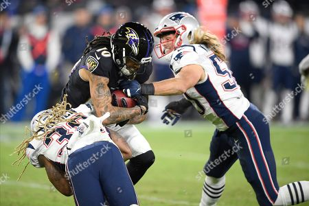 Baltimore Ravens' Chris Moore (10) returns a kickoff from the New England Patriots as Brandon Bolden, left, and Chase Winovich move in for the hit during the second half of an NFL football game, in Baltimore