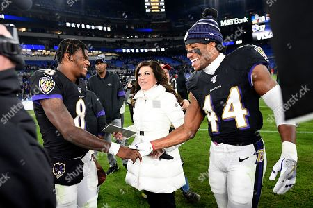 Baltimore Ravens quarterback Lamar Jackson (8) shakes hands with cornerback Marlon Humphrey (44) as reporter Michele Tafoya looks on after an NFL football game against the New England Patriots, in Baltimore. The Ravens won 37-20