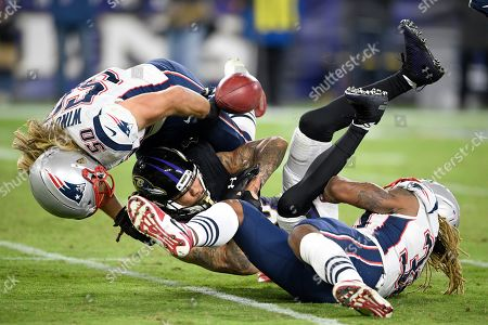 Baltimore Ravens' Chris Moore, center, fumbles a kickoff return as New England Patriots defensive end Chase Winovich (50) and running back Brandon Bolden make the hit during the second half of an NFL football game, in Baltimore. The Ravens recovered the fumble