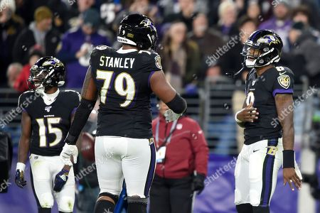 Baltimore Ravens quarterback Lamar Jackson (8) celebrates his touchdown run against the New England Patriots with offensive tackle Ronnie Stanley (79) during the first half of an NFL football game, in Baltimore