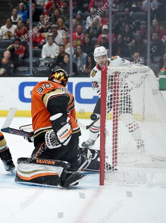 Chicago Blackhawks right wing Alex DeBrincat, right, scores a goal against Anaheim Ducks goalie Ryan Miller (30) during the first period of an NHL hockey game in Anaheim, Calif