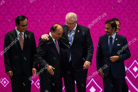 Stock Picture of Australian Prime Minister Scott Morrison (C-R) embraces Prime Minister of Vietnam Nguyen Xuan Phuc (C-L) as Thailand Prime Minister Prayut Chan-o-cha (L) and Sultan of Brunei Hassanal Bolkiah (R) look on during a family photo session during the 14th East Asia Summit at the 35th Association of Southeast Asian Nations (ASEAN) Summit at IMPACT Muang Thong Thani in Nonthaburi province, Thailand, 04 November 2019. Thailand is hosting the 35th ASEAN Summit, which will run from 02 to 04 November 2019.