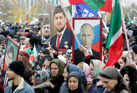People hold portraits of Russian President Vladimir Putin and Chechen leader Ramzan Kadyrov during a rally marking National Unity Day in Grozny, southern Russia