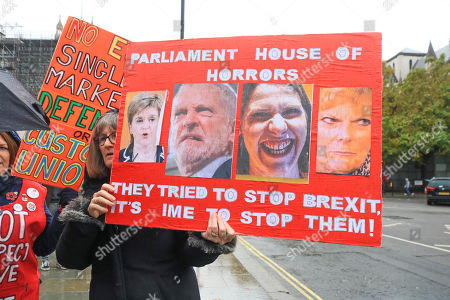 A Pro Brexit protester outside Parliament holds a placard with pictures of remain politicians Nicola Sturgeon, Jeremy Corbyn, Jo Swinson and Anna Soubry