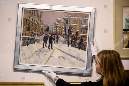 A staff member poses with 'Snow in the City of London', by Ken Howard RA, GBP18,500. The painting is the original artwork for the Royal Academy of Arts Christmas card