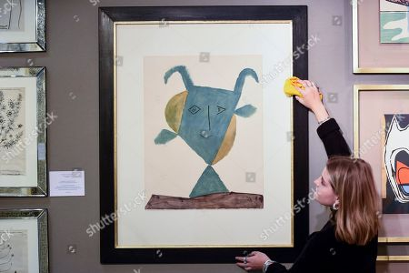 A staff member poses with a colour lithograph of 'Faunes et Flore d'Antibes', 1960, by Pablo Picasso, GBP4,850