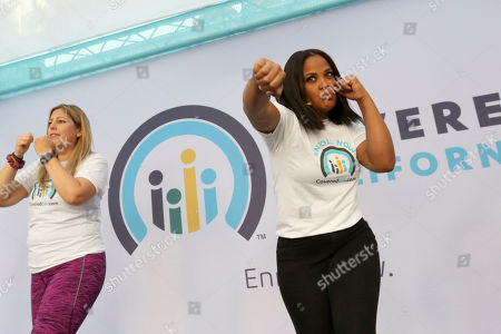 Laila Ali, world-class athlete, right, leads fitness demonstrations to raise awareness of Open Enrollment at the Covered California Open Enrollment Kickoff event at The Bloc, in Downtown Los Angeles, Calif