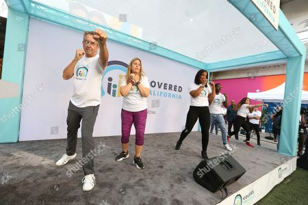 Stock Image of Peter V. Lee, Laila Ali. Laila Ali, world-class athlete, third from left, and Covered California Executive Director, Peter V. Lee, left, lead fitness demonstrations to raise awareness of Open Enrollment at the Covered California Open Enrollment Kickoff event at The Bloc, in Downtown Los Angeles, Calif