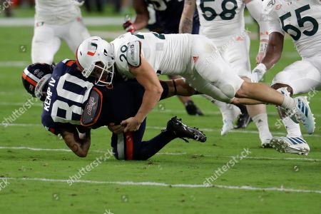 Virginia running back Billy Kemp IV (80) is tackled by Miami defensive back Jimmy Murphy on a punt return during the first half of an NCAA college football game, in Miami Gardens, Fla