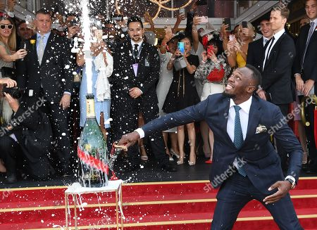 Jamaican former Olympic athlete Usain Bolt (R) reacts as he opens a bottle of champagne during Melbourne Cup Day at Flemington Racecourse in Melbourne, Australia, 05 November 2019.