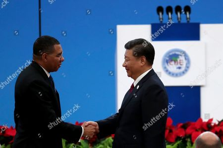 Chinese President Xi Jinping, at right shakes hands with Jamaica's Prime Minister Andrew Holness at the opening ceremony of the China International Import Expo in Shanghai on . The sprawling import fair into its second year is meant to demonstrate China's willingness to open its domestic markets