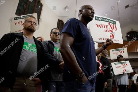 """Stock Image of People wearing """"Save The Paseo"""" shirts stand among attendees at a rally to keep a street named in honor of Dr. Martin Luther King Jr. at Paseo Baptist Church in Kansas City, Mo. In January, the City Council voted to rename one of the city's main boulevards, The Paseo, after King, but many in the community want the old name back. A petition drive put the issue on the Nov. 5 ballot pitting neighbors against each other"""