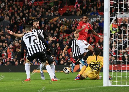 Partizan Belgrade goalkeeper Vladimir Stojkovic makes a save from Marcus Rashford of Manchester United