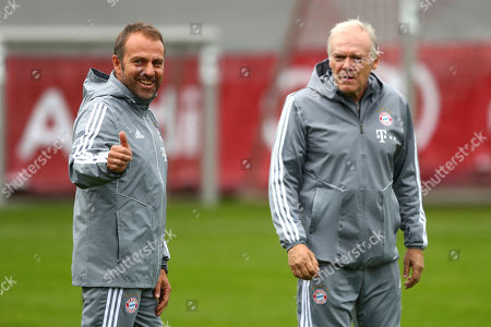 New Bayern Munich head coach Hansi Flick, left, and his assistant Hermann Gerland arrive for a training session prior to the Champions League group B soccer match between Bayern Munich and Olympiakos in Munich, Germany, . Bayern will face Olympiakos on Wednesday