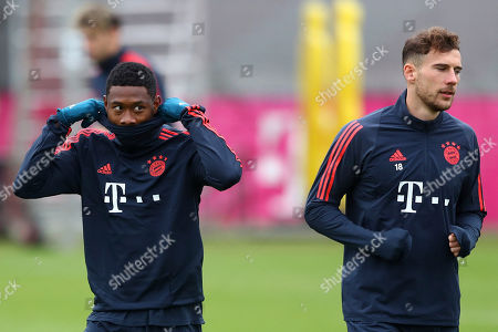 Bayern's David Alaba, left, covers his face besides team mate Leon Goretzka during a training session prior to the Champions League group B soccer match between Bayern Munich and Olympiakos in Munich, Germany, . Bayern will face Olympiakos on Wednesday