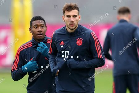 Bayern's David Alaba, left and team mate Leon Goretzka warm up during a training session prior to the Champions League group B soccer match between Bayern Munich and Olympiakos in Munich, Germany, . Bayern will face Olympiakos on Wednesday