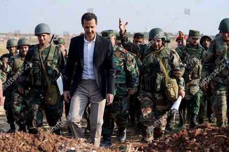 Syrian President Bashar al-Assad listening to army soldiers in al-Habit on the southern edges of the Idlib province.