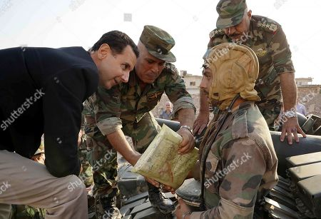 Syrian President Bashar al-Assad talking to Syrian soldiers in al-Habit on the southern edges of the Idlib province. Assad visited government troops on the front line with Jihadists in Idlib, his first visit to the northwestern province since the start of the conflict.