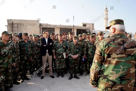 Syrian President Bashar al-Assad posing for a picture with Syrian soldiers in al-Habit on the southern edges of the Idlib province.