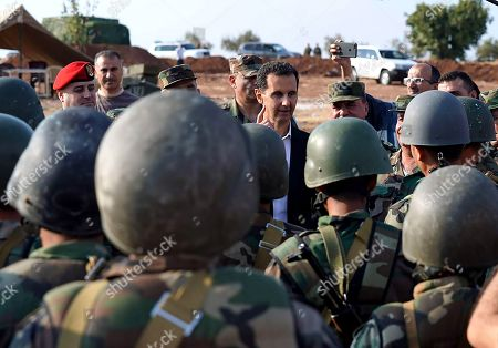 Syrian President Bashar al-Assad talking to army soldiers in al-Habit on the southern edges of the Idlib province.