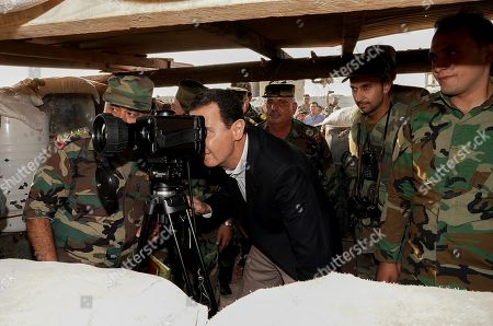 Syrian President Bashar al-Assad looking through a monocular on the frontline during a visit to soldiers in al-Habit on the southern edges of the Idlib province.