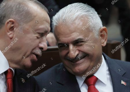 Stock Photo of Recep Tayyip Erdogan, Binali Yildirim. Turkish President Recep Tayyip Erdogan, left, speaks with Binali Yildirim, his former last prime minister, at the Parliament, in Ankara, . Erdogan called on Russia and the United States on Tuesday to keep to their promises to ensure that Syrian Kurdish fighters pull out of Syrian borders areas with Turkey
