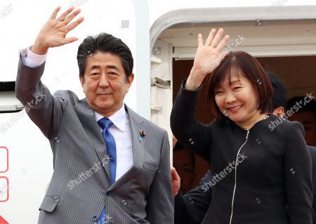 Japanese Prime Minister Shinzo Abe (L) accompanied by his wife Akie (R) leaves Toyota International Airport