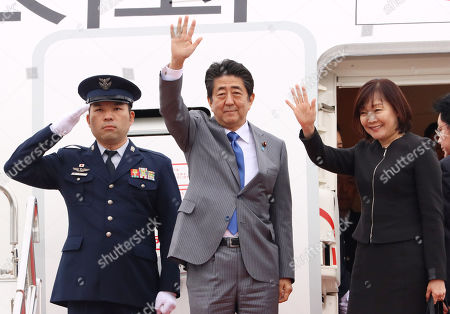 Stock Picture of Japanese Prime Minister Shinzo Abe (L) accompanied by his wife Akie (R) leaves Toyota International Airport