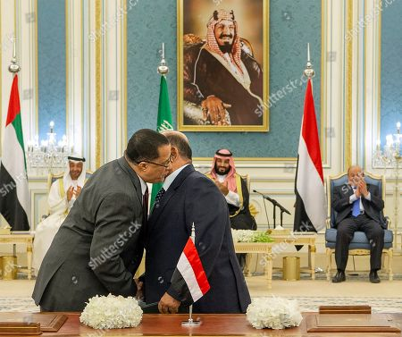 In this photo released by the Saudi Royal Palace, Yemeni Southern Transitional Council member and former Aden Governor Nasser al-Khabji, left, and Yemen's deputy Prime Minister Salem al-Khanbashi greet each other before signing a power-sharing deal witnessed by Yemen's president, Abed Rabbo Mansour Hadi, background right, Saudi Arabia's Crown Prince Mohammed bin Salman, center, and Dhabi's Crown Prince, Mohammed bin Zayed Al Nahyan, in Riyadh, Saudi Arabia, . Yemen's internationally recognized government signed a power-sharing deal with Yemeni separatists that are backed by the United Arab Emirates. A picture of Saudi Arabia's founder late King Abdul Aziz Al Saud hangs on wall