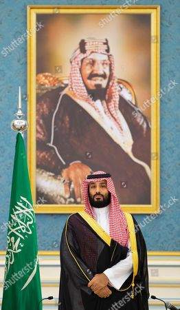 In this photo released by Saudi Royal Palace, Saudi Arabia's Crown Prince Mohammed bin Salman attends the signing a power-sharing deal between Yemen's internationally recognized government and Yemeni separatists that are backed by the United Arab Emirates, in Riyadh, Saudi Arabia, . At top is a picture of Saudi Arabia's founder late King Abdul Aziz Al Saud