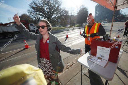 Anna wilson, adam bollinger. Voter Anna Wilson, left, reacts after dropping off her ballot at the pick-up site of the Denver Election Division outside the City/County Building early, in Denver. Election judge Adam Bollinger, right, looks on