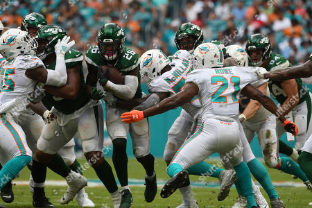 Raekwon McMillan #52, Eric Rowe #21, Vince Biegel #47, and Jerome Baker #55 of Miami tackles Le�Veon Bell #26 of New York during the NFL football game between the Miami Dolphins and New York Jets at Hard Rock Stadium in Miami Gardens FL. The Patriots defeated the Dolphins 26-18