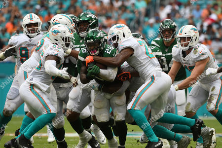 Raekwon McMillan #52, Eric Rowe #21, Vince Biegel #47, and Jerome Baker #55 of Miami tackles Leâ??Veon Bell #26 of New York during the NFL football game between the Miami Dolphins and New York Jets at Hard Rock Stadium in Miami Gardens FL. The Patriots defeated the Dolphins 26-18