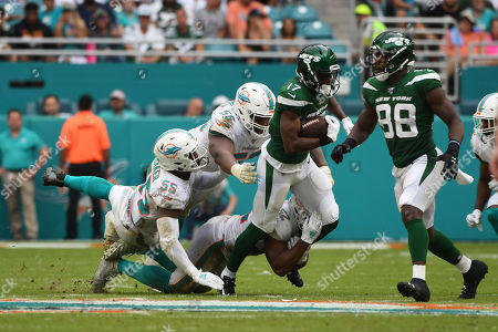 Raekwon McMillan #52, Davon Godchaux #56, and Jerome Baker #55 of Miami tackles Vyncint Smith #17 of New York during the NFL football game between the Miami Dolphins and New York Jets at Hard Rock Stadium in Miami Gardens FL. The Patriots defeated the Dolphins 26-18