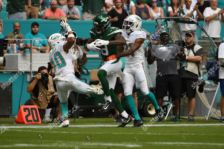 Demaryius Thomas #18 of New York is pursued by Nik Needham #40 and Eric Rowe #21 of Miami during the NFL football game between the Miami Dolphins and New York Jets at Hard Rock Stadium in Miami Gardens FL. The Patriots defeated the Dolphins 26-18