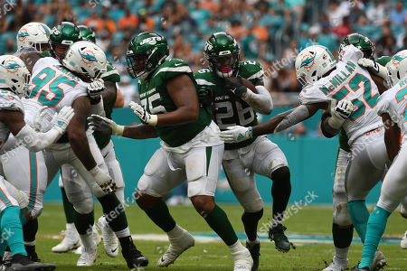 Raekwon McMillan #52 of Miami reaches for Leâ??Veon Bell #26 of New York during the NFL football game between the Miami Dolphins and New York Jets at Hard Rock Stadium in Miami Gardens FL. The Patriots defeated the Dolphins 26-18