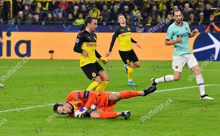 Inter Milan's goalkeeper Samir Handanovic, bottom, saves on Dortmund's Mario Gotze during the Champions League group F soccer match between Borussia Dortmund and Inter Milan, in Dortmund, Germany