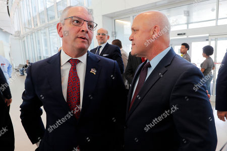 Louisiana Gov. John Bel Edwards, left, greets former New Orleans Mayor Mitch Landrieu before a ribbon cutting ceremony for the opening the newly built main terminal of the Louis Armstrong New Orleans International Airport in Baton Rouge, La