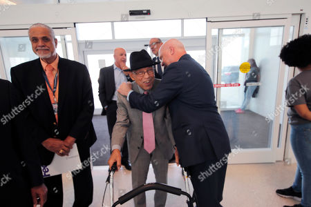 Stock Picture of Former New Orleans Mayor Mitch Landrieu, right, greets Dr. Norman C. Francis, former President of Xavier University of Louisiana, as he arrives at a ribbon cutting ceremony for the opening the newly built main terminal of the Louis Armstrong New Orleans International Airport in Baton Rouge, La