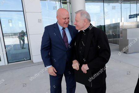 Stock Image of Former New Orleans Mayor Mitch Landrieu, left, greets New Orleans Archbishop Gregory Aymond as they arrive at a ribbon cutting ceremony for the opening the newly built main terminal of the Louis Armstrong New Orleans International Airport in Baton Rouge, La