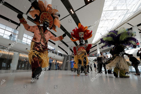Members of the Zulu Social Aid & Pleasure Club Tramps lead a second line parade during festivities for the opening of the newly built main terminal of the Louis Armstrong New Orleans International Airport in Kenner, La
