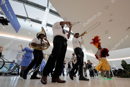 A brass band leads a second line parade during festivities for the opening of the newly built main terminal of the Louis Armstrong New Orleans International Airport in Kenner, La