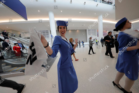 Women dressed as flight attendants dance and wave handkerchiefs to a second line parade during festivities for the opening of the newly built main terminal of the Louis Armstrong New Orleans International Airport in Kenner, La