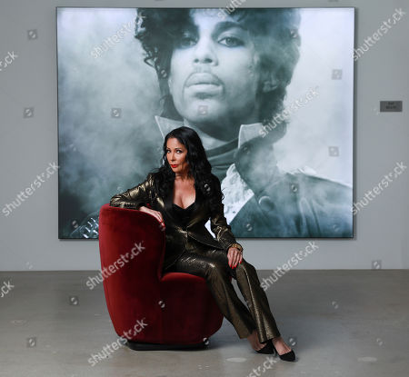 "Apollonia Kotero poses for a portrait in front of a photo of Prince at Warner Music Group in Los Angeles on. Kotero, who recorded Prince's ""Sex Shooter,"" is one of several artists who spoke with The Associated Press about their experience working with the artist. The song is included on a posthumous album of Prince's music, ""Originals,"" due out this month"