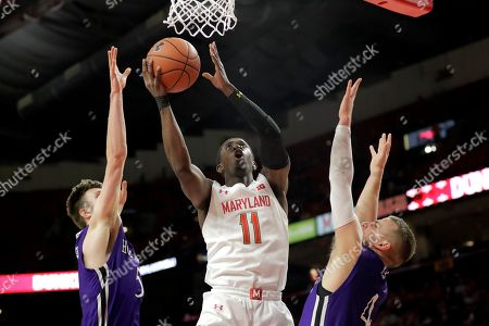 Stock Image of Maryland guard Darryl Morsell (11) goes up for a shot against Holy Cross forward Connor Niego, left, and guard Austin Butler during the first half of an NCAA college basketball game, in College Park, Md