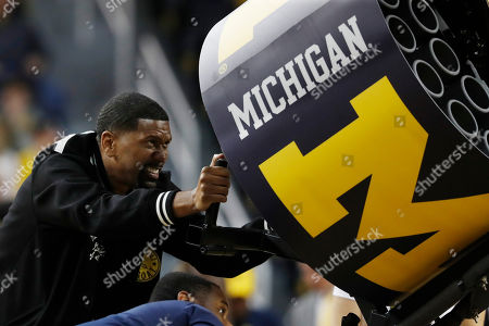 Stock Photo of Jalen Rose mans the T-shirt cannon during the second half of an NCAA college basketball game between Michigan and Appalachian State, in Ann Arbor, Mich
