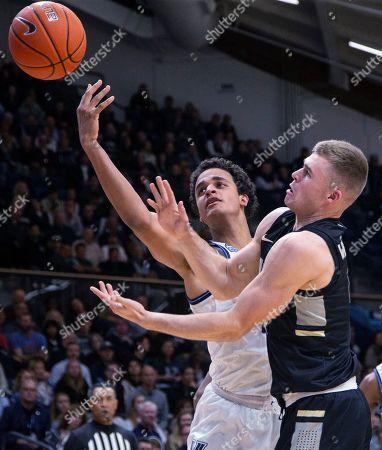 Stock Image of Villanova forward Jeremiah Robinson-Earl (24) and Army forward Chris Mann (4) reach for a rebound during the second half of an NCAA college basketball game, in Villanova, Pa. Villanova won 97-54