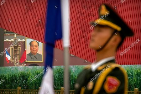An honor guard member stands at attention as French and Chinese flags fly near the large portrait of Chinese Leader Mao Zedong on Tiananmen Gate before a welcome ceremony for French President Emmanuel Macron in Beijing