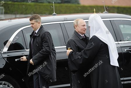 Russian President Vladimir Putin (center) and Patriarch Kirill of Moscow and all Rus' (right) during a flower-laying ceremony at the monument to the heroes of the 1612 people's militia K. Minin and D. Pozharsky on Red Square.